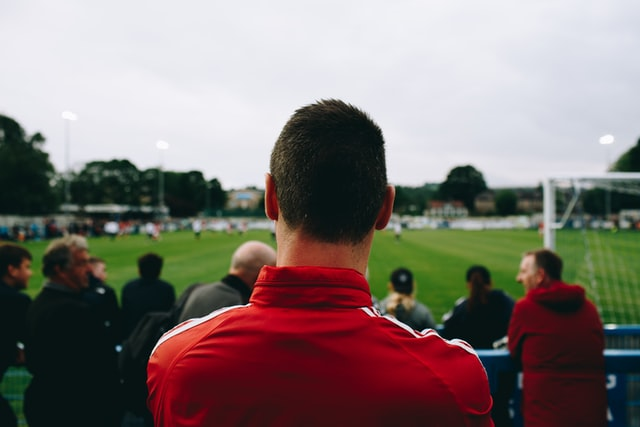 Man standing while watching football during daytime